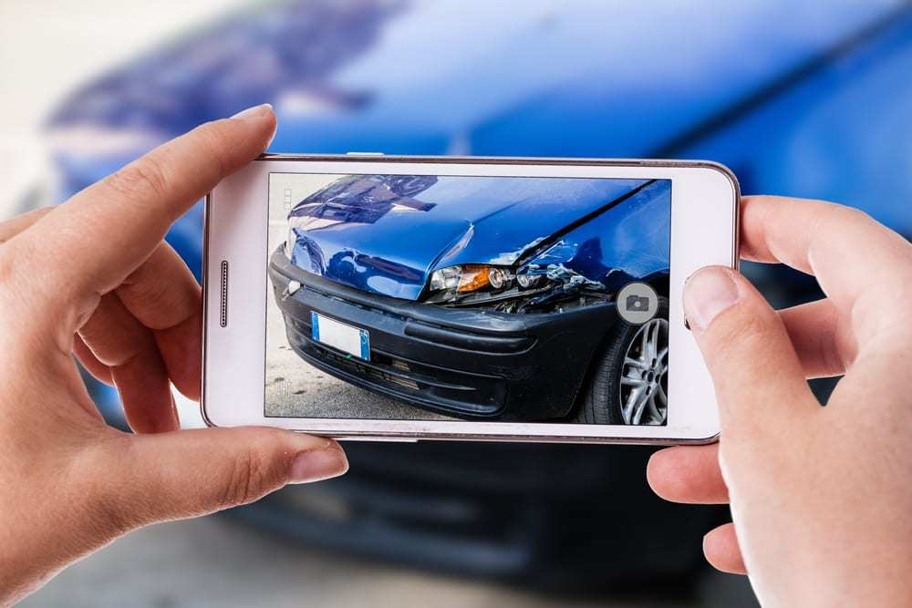 a woman using a smart phone to take a photo of the damage to her car caused by a car crash