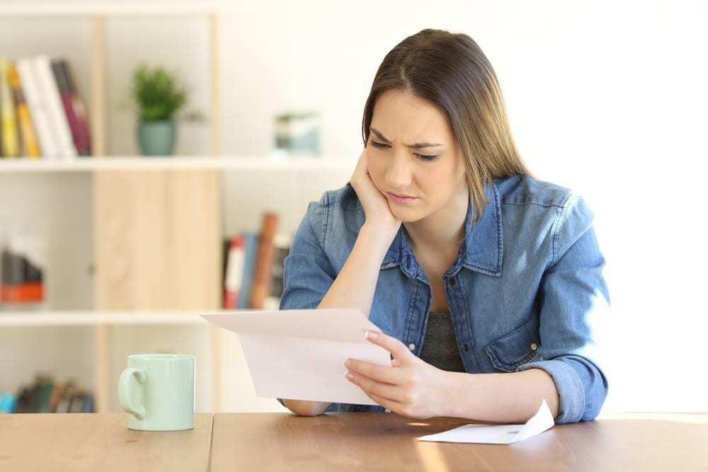Worried woman reading a letter from her insurance company