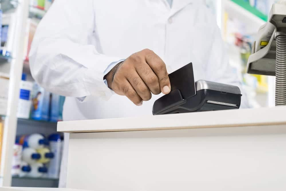 Close-up of Pharmacist Swiping Credit Card On Reader