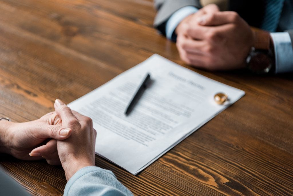 close-up of hands as couple sits across from one another, divorce papers between them