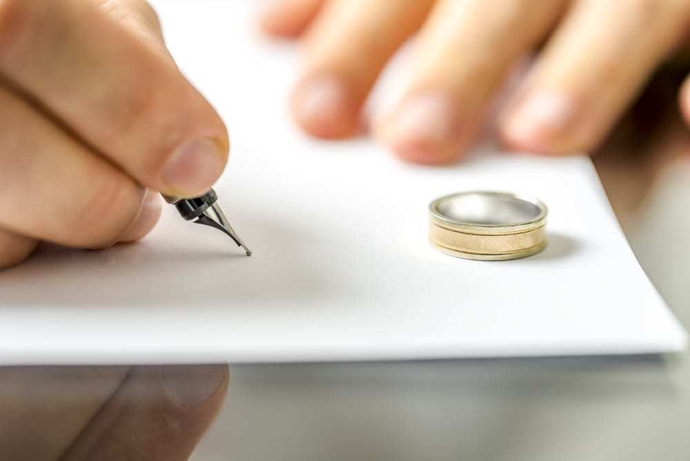 Close-up of hand signing paper, a wedding ring sits on the paper
