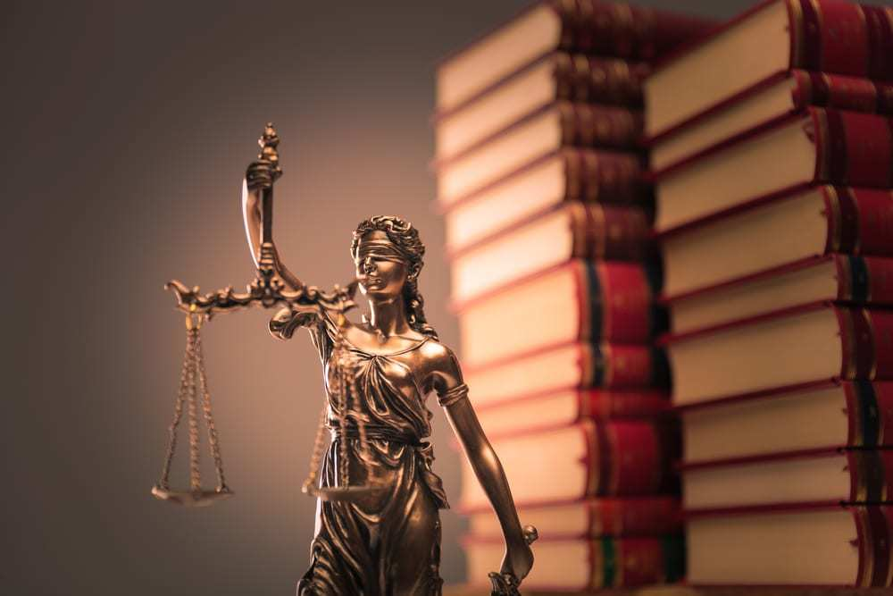 Lady Justice statue in front of law books