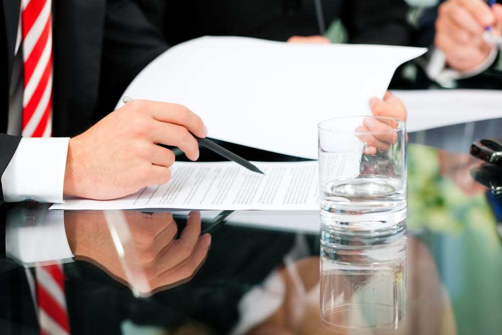 Close-up of man at conference table reviewing documents