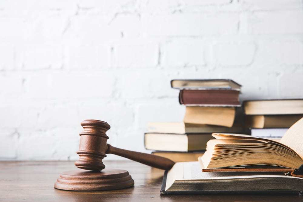 Open judicial books and gavel on wooden table