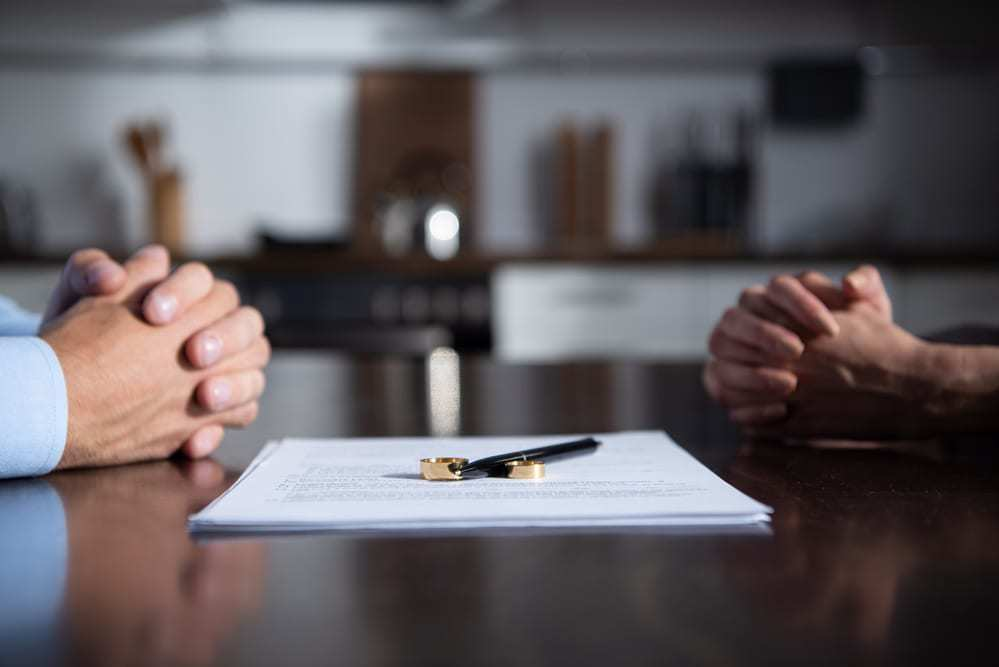 Partial view of couple sitting at table with clenched hands, divorce papers and rings in between