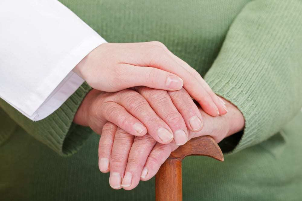 Senior hands on top of cane, young doctor's hand on top