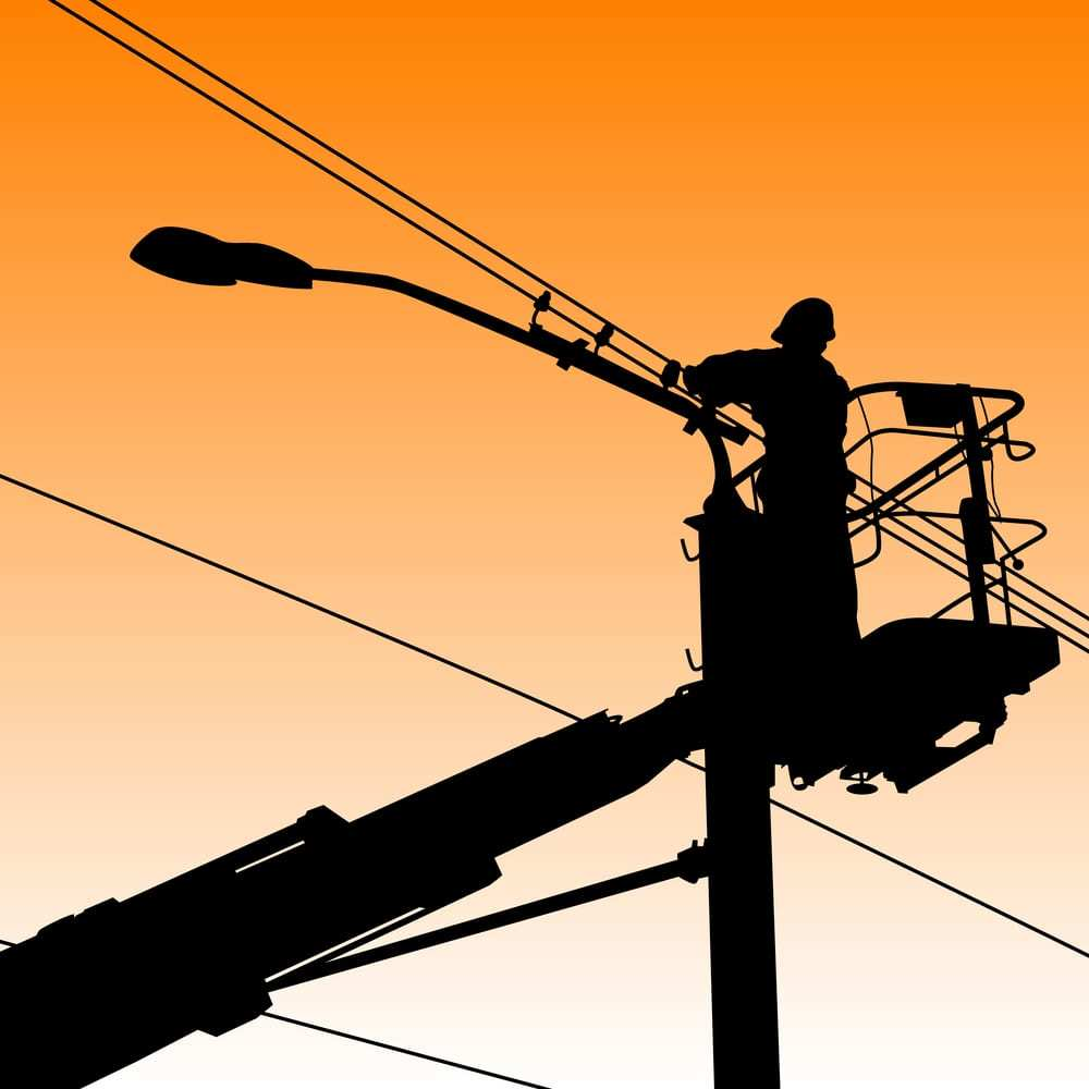 Silhouette of electrician working on a power pole at sunset