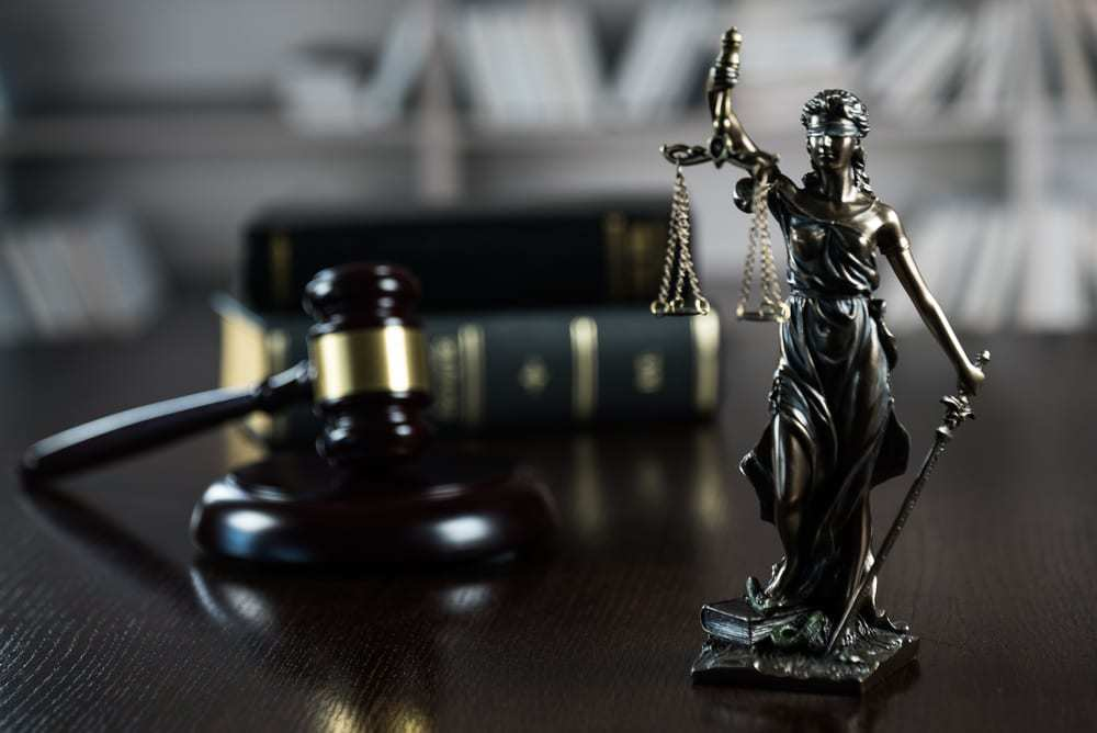 """""""justice is blind"""" statue featuring woman holding scales, gavel and books behind her"""