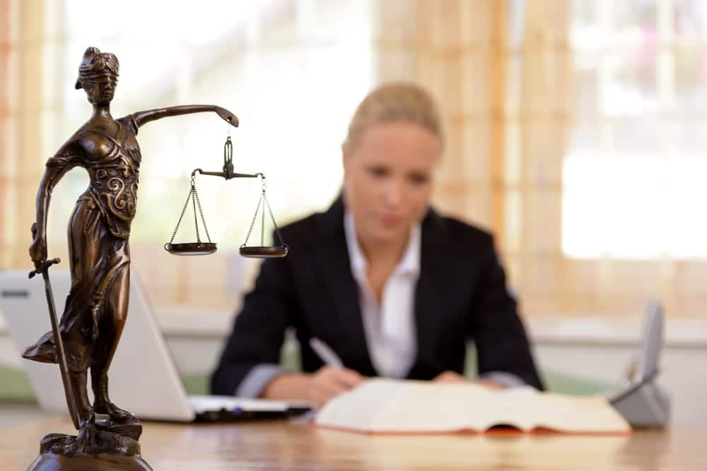 Scales of justice on desk, attorney working in background