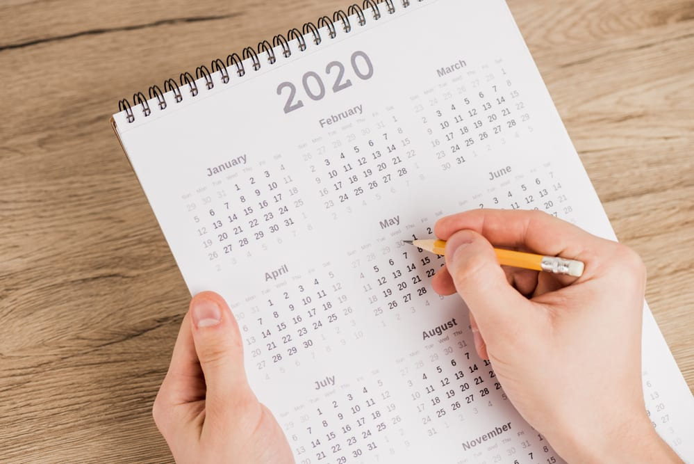 Close-up of hand holding pencil above 2020 year calendar