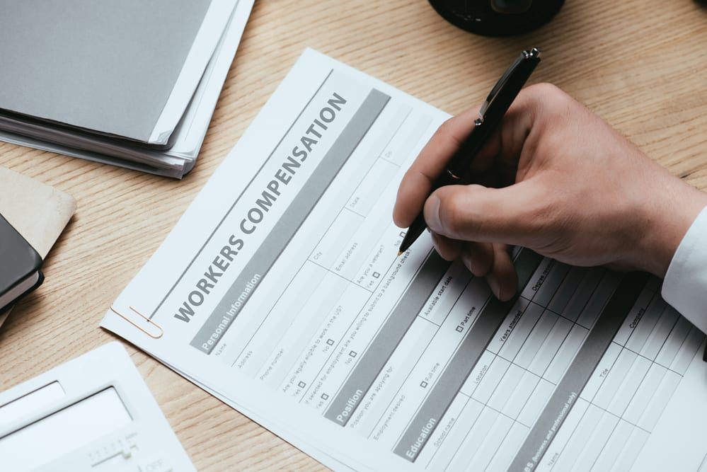 Close-up of hand filling out workers' compensation form
