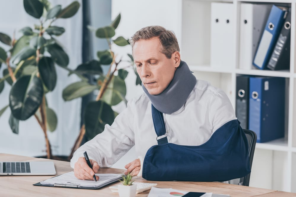 Injured man with neck brace and sling signing paper at desk