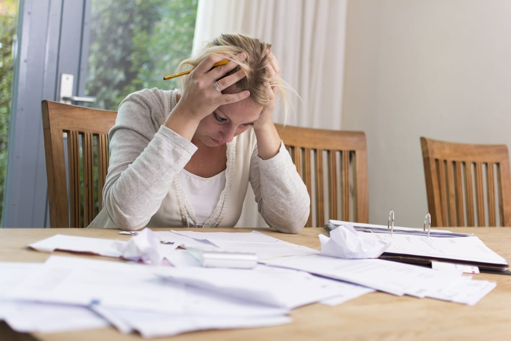 Stressed woman looking down at table filled with papers