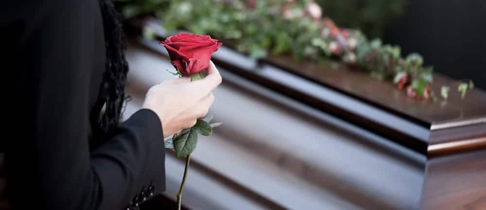 Woman holding red rose beside coffin