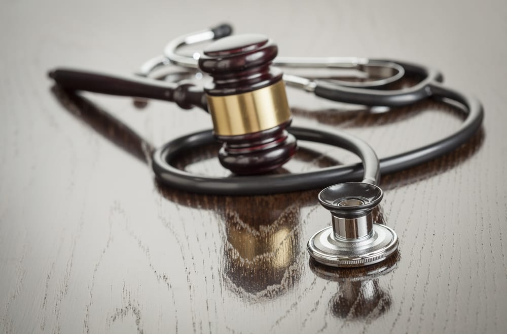Stethoscope and gavel on reflective table