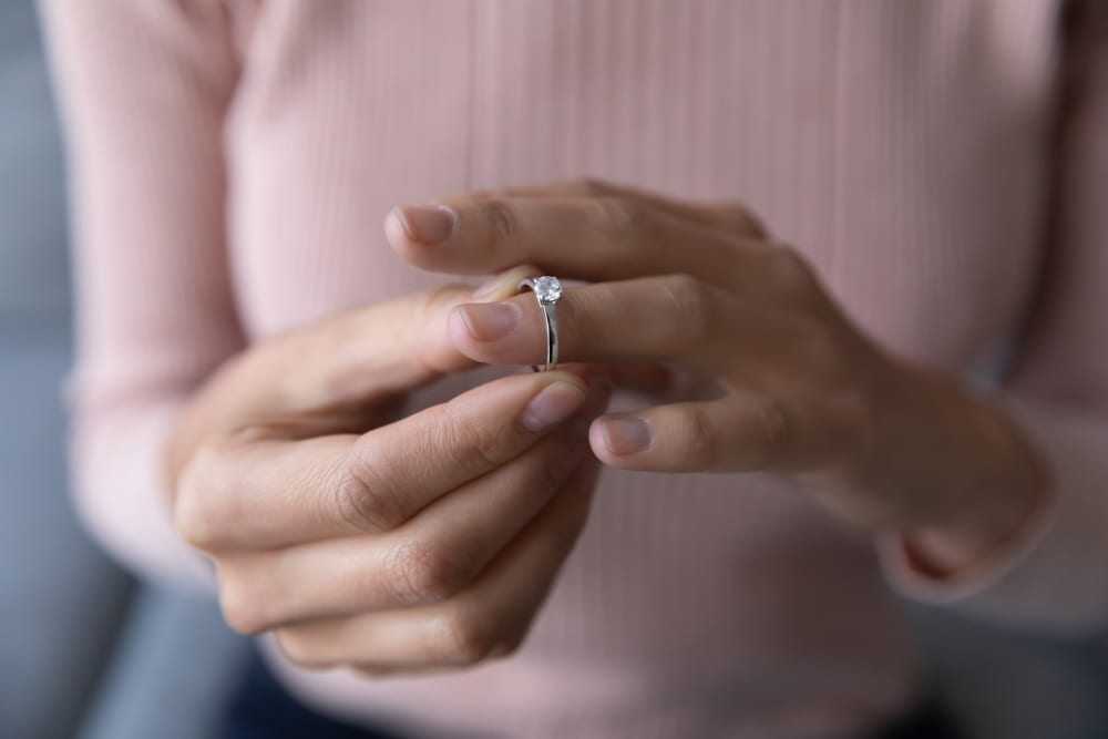 Close-up of woman removing engagement ring