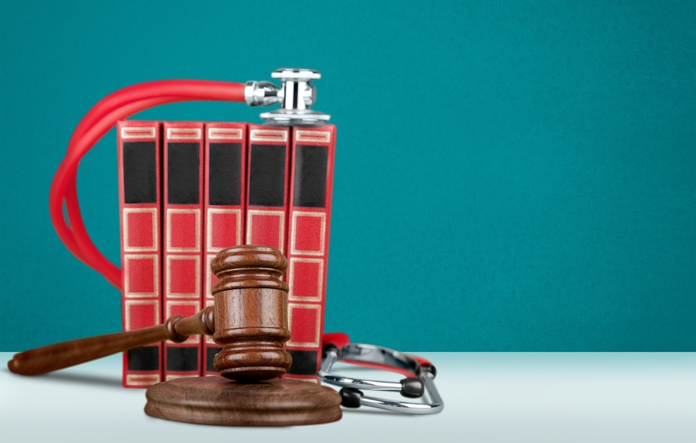 Gavel, stethoscope, and books with turquoise background