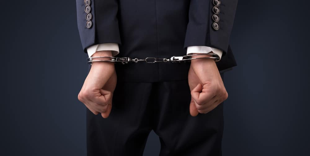 Close-up of young man's hands in handcuffs behind his back