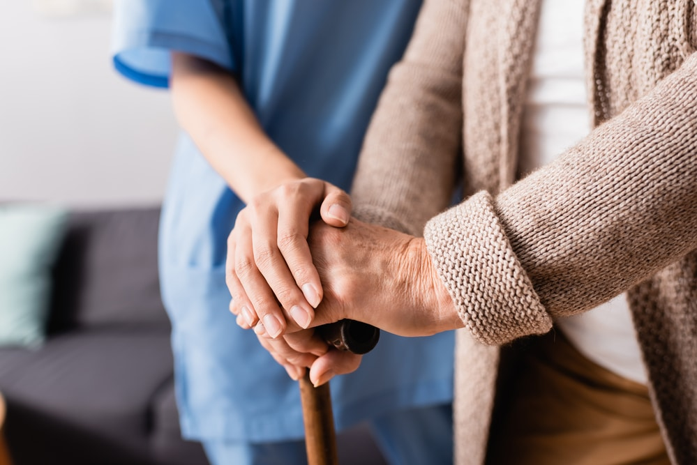 Close-up of young nurse's hands on top of senior woman's hands on cane